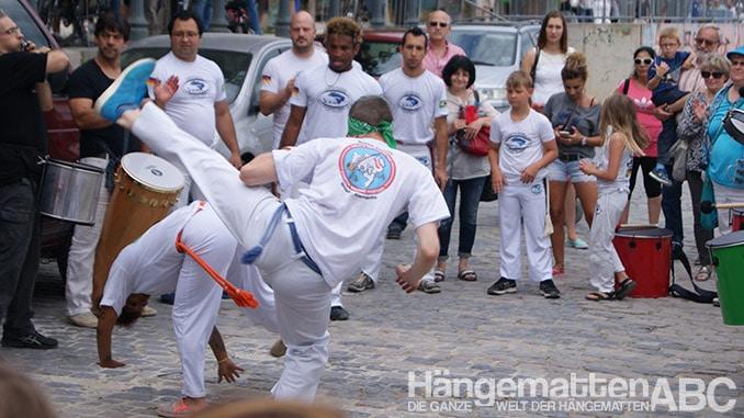 Zwei Capoeira Kämpfer inmitten von Trommlern